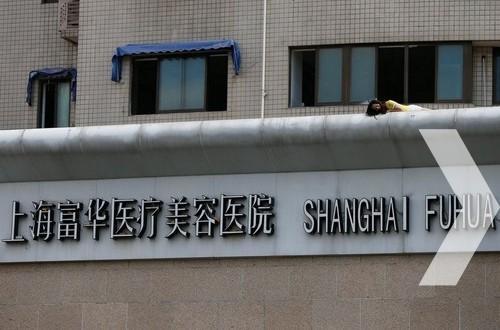 2013年9月4日,上海,一名女子爬上位于江宁路、海防路口附近一家整形医院楼顶做出危险举动,趴在店招上。