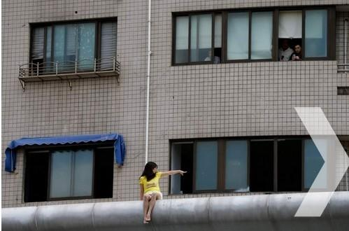 9月4日上午,上海江宁路海防路路口,一女子在某整容医院顶楼欲寻短见,后被谈判专家劝下。据悉,女子去年做隆胸手术后出现并发症,植入假体被取出,又发现乳房有肿块。院方表示无法接受天价索赔,希望通过第三方调解或医疗事故鉴定解决。图为该女子在医院楼顶。