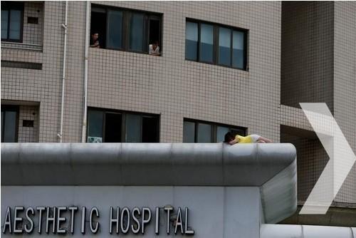 据悉,事发的美容医院是一栋建筑物的裙房。这名身穿黄衣的女子今天上午来到这家医院门前,阻止人员进出。在9月4日11时左右,该女子爬上了这家美容医院的六楼楼顶,时而坐在楼顶边缘,时而趴在店招上,举动引起围观。