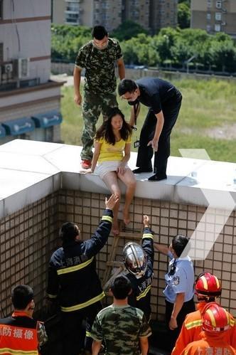 12时左右,该名女子在谈判专家的不断劝说下终于同意离开楼顶。在警方及消防人员的帮助下通过梯子从高处爬下。图为谈判专家将女子劝下。