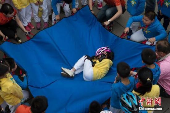 5月12日,来自北京市第十八中学附属实验小学的学生在观看应急安全教育儿童剧《奇妙梦旅行》前,在中国儿童剧院前广场体验了由   青岛   红十字天使救援队等相关单位组织的,包括心肺复苏、灭火器使用、模拟地震等多项应急安全体验活动.